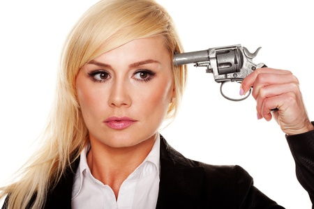 Young suicidal blonde woman holding a gun to her head isolated on white photo