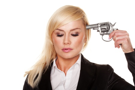 attempted: Young professional woman with downcast eyes holding a gun to her head in an attempted suicide or in a demonstration