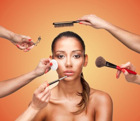makeover: Conceptual beauty and fashion image of the hands of several beauticians and stylists holding their respective equipment giving a glamour makeover to a beautiful woman Stock Photo