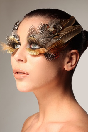 enhancing: Decorative feather make-up like the wing of a bird enhancing and surrounding the green eyes of a beautiful woman as she looks sideways off camera
