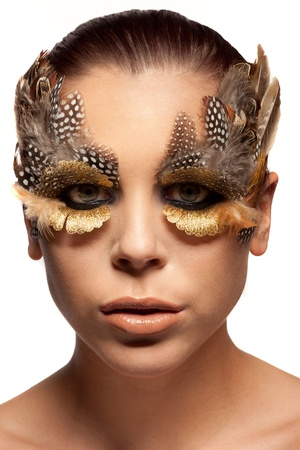 enhancing: Beautiful woman wearing dramatic creative make-up of the feathers of wild birds framing and enhancing her eyes