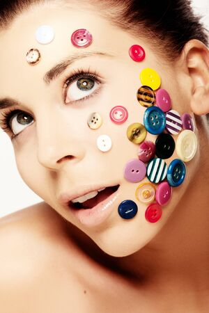 stuck up: Close up portrait of beautiful woman with various colorful buttons on her face Stock Photo