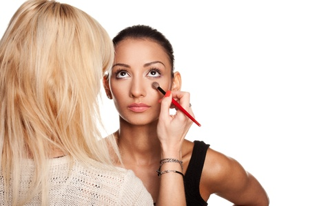 Professional makeup artist applying makeup to models face - isolated on white photo