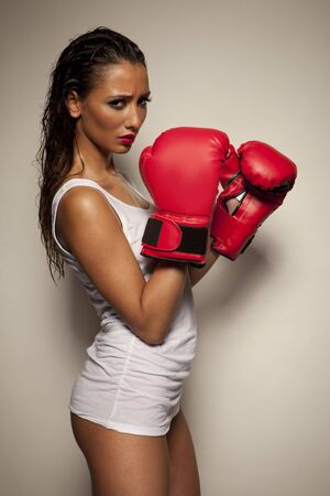 perspiring: Sexy woman with red boxing gloves and dangerous facial expressions posing on gray background