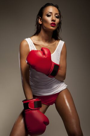 Seductive woman boxer glistens with sweat as she takes a break from traning at the gym photo