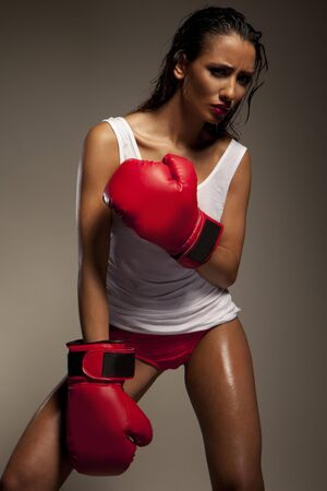 human sexual activity: Studio shot of sexy female fighter with red boxing gloves Stock Photo