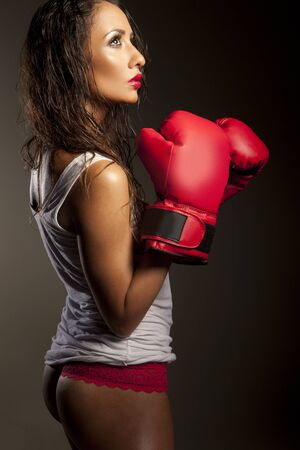 psych: Sexy woman boxer with her hair damp from perpiration pausing during training showing her cute bum Stock Photo