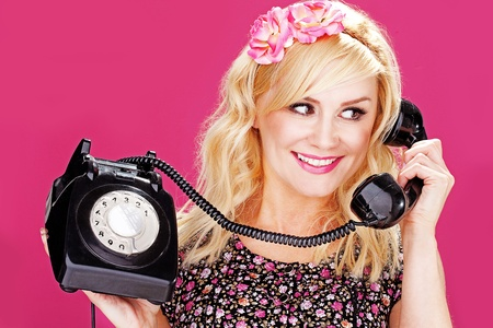 retro phone: Young woman talking on an old dial up telephone