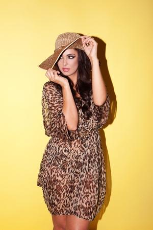 huella animal: Mujer con estilo elegante que llevaba un traje de animal print de moda con un sombrero de paja de ala ancha
