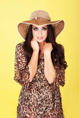 Sexy beautiful brunette in stylish straw hat and animal print dress posing against a yellow studio background photo