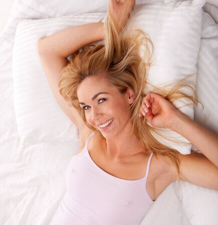 blonde happy woman relaxing on bed using her tablet photo