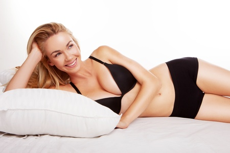 blonde woman on bed wearing black lingerie