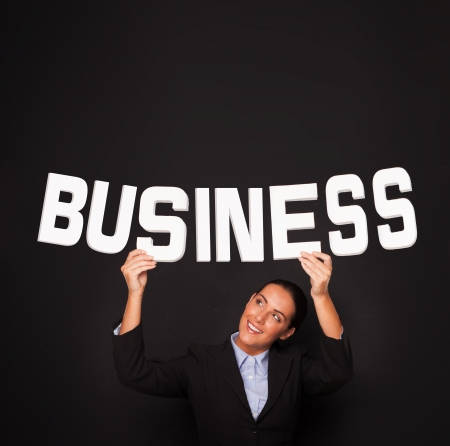 entrepeneur: Smiling beautiful professional businesswoman holding up the word BUSINESS in white lettering on a black studio background