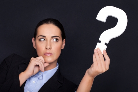 Beautiful businesswoman with a thoughtful expression holding a white question mark in her hand against a black studio background Foto de archivo