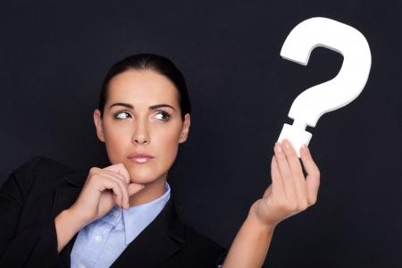 interrogativa: Mujer de negocios hermosa con una expresión pensativa que sostiene un signo de interrogación blanco en la mano sobre un fondo negro del estudio