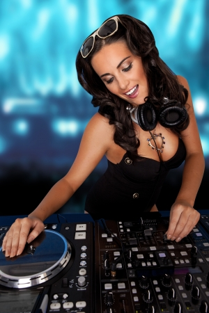 Sexy curvy DJ with her sunglasses on her head and earphones around her next laughing while mixing music at her deck at a party or disco photo