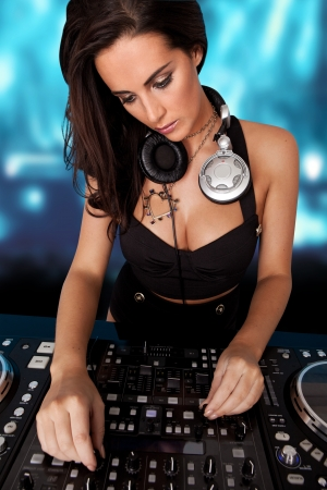 turntables: Beautiful busty DJ with her headphones around her neck standing at her deck mixing sound in a nightclub or disco Stock Photo