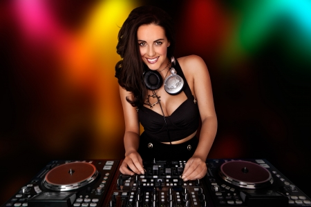 turntable: Beautiful busty DJ smiling at the camera with her headphones around her neck standing at her deck mixing sound in a nightclub or disco with coloured party lights behind her Stock Photo