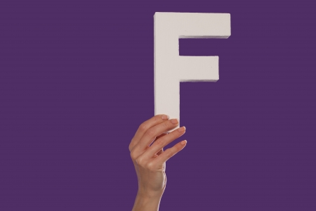 majuscule: Female hand holding up the uppercase capital letter F isolated against a purple background conceptual of the alphabet, writing, literature and typeface