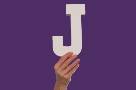 majuscule: Female hand holding up the uppercase capital letter J isolated against a purple background conceptual of the alphabet, writing, literature and typeface Stock Photo