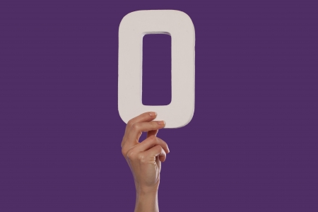 null: Female hand holding up the number 0 against a purple background conceptual of numbers, measurement, amount, quantity, accounting and mathematics Stock Photo