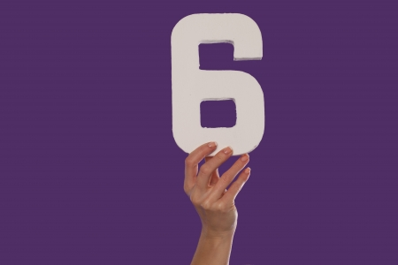 number 6: Female hand holding up the number 6 against a purple background conceptual of numbers, measurement, amount, quantity, accounting and mathematics Stock Photo