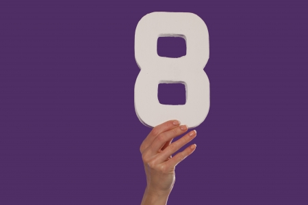 Female hand holding up the number 8 against a purple background conceptual of numbers, measurement, amount, quantity, accounting and mathematics photo