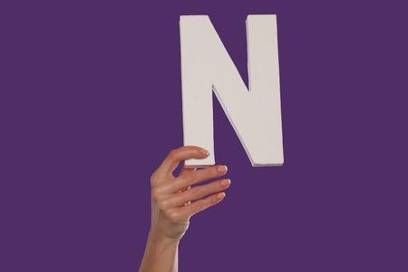 majuscule: Female hand holding up the uppercase capital letter N isolated against a purple background conceptual of the alphabet, writing, literature and typeface