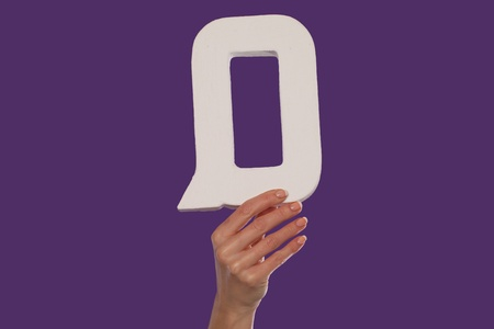 majuscule: Female hand holding up the uppercase capital letter Q isolated against a purple background conceptual of the alphabet, writing, literature and typeface