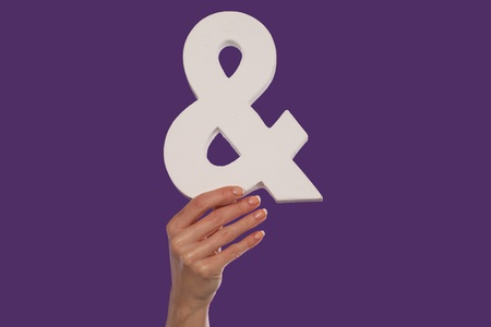 jointly: Female hand holding up a white ampersand symbol isolated against a purple background signifying plus, and, in conjunction with, or jointly Stock Photo