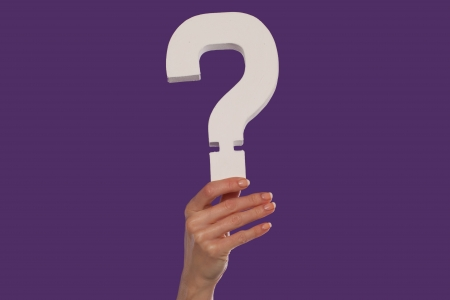 Female hand holding up a white question mark against a purple background conceptual of questions, query, why or what. photo