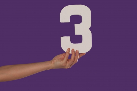division: Female hand holding up the number 3 against a purple background conceptual of numbers, measurement, amount, quantity, accounting and mathematics Stock Photo