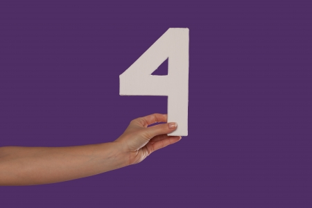 Number 4: Female hand holding up the number 4 against a purple background conceptual of numbers, measurement, amount, quantity, accounting and mathematics