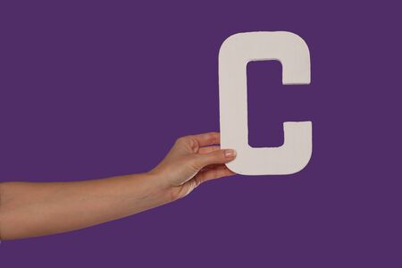 aloft: Female hand holding up the uppercase capital letter C isolated against a purple background conceptual of the alphabet, writing, literature and typeface