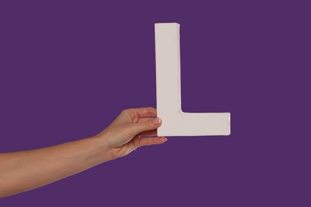 majuscule: Female hand holding up the uppercase capital letter L isolated against a purple background conceptual of the alphabet, writing, literature and typeface Stock Photo