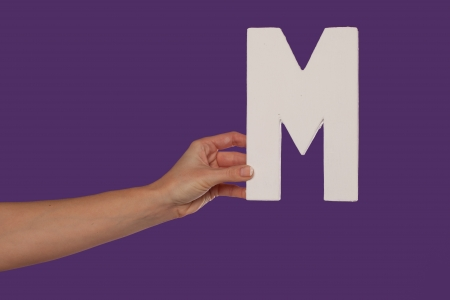 majuscule: Female hand holding up the uppercase capital letter M isolated against a purple background conceptual of the alphabet, writing, literature and typeface Stock Photo