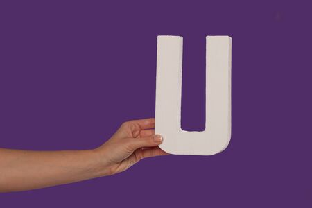 majuscule: Female hand holding up the uppercase capital letter U isolated against a purple background conceptual of the alphabet, writing, literature and typeface Stock Photo