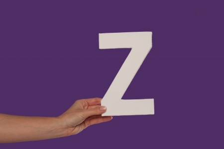 majuscule: Female hand holding up the uppercase capital letter Z isolated against a purple background conceptual of the alphabet, writing, literature and typeface