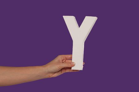 majuscule: Female hand holding up the uppercase capital letter Y isolated against a purple background conceptual of the alphabet, writing, literature and typeface Stock Photo