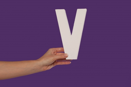 majuscule: Female hand holding up the uppercase capital letter V isolated against a purple background conceptual of the alphabet, writing, literature and typeface
