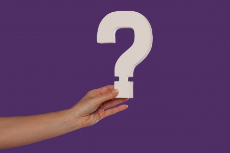unclear: Female hand holding up a white question mark against a purple background conceptual of questions, query, why or what. Stock Photo