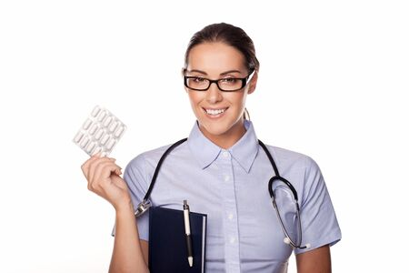 dispensing: Beautiful female doctor dispensing a pack of tablets which she is holding up in her hand with a smile isolated on white Stock Photo