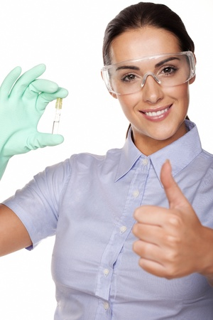 Beautiful smiling young female lab technician giving a thumbs up of success while holding up a test tube in her gloved hand isolated on white photo