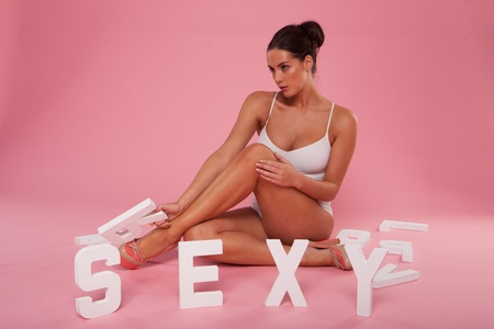 shapely legs: Beautiful alluring brunette woman posing in her bathing costume on the floor with the word SEXY in white lettering against a pink background