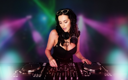 Glamorous sexy busty DJ at work mixing sound on her decks at a party or night club with colourful strobe light background