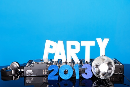 disc jockey: PARTY 2013 background with DJ music mixing deck, mirrored disco ball and lettering against a blue background with copyspace