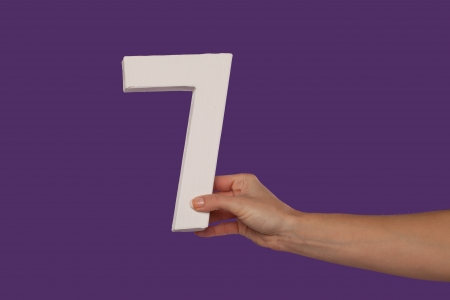 communicate concept: Female hand holding up the number 7 against a purple background conceptual of numbers, measurement, amount, quantity, accounting and mathematics