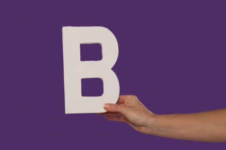 majuscule: Female hand holding up the uppercase capital letter B isolated against a purple background conceptual of the alphabet, writing, literature and typeface