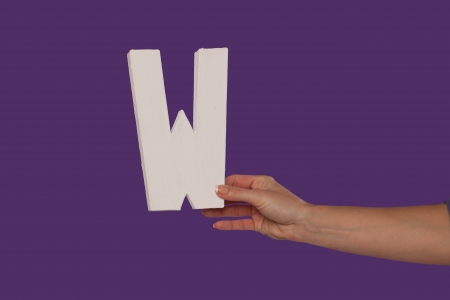 majuscule: Female hand holding up the uppercase capital letter W isolated against a purple background conceptual of the alphabet, writing, literature and typeface