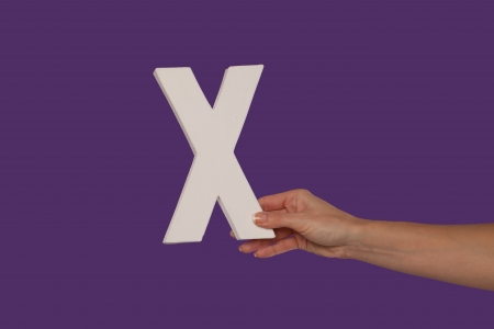 majuscule: Female hand holding up the uppercase capital letter X isolated against a purple background conceptual of the alphabet, writing, literature and typeface
